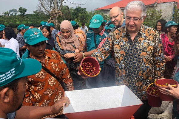 CEO International Islamic Trade Finance Corporation (ITFC) Eng Hani Salem Sonbol menuangkan kopi dalam mesin pengupas di Kecamatan Naman Teran Kabupaten Karo Sumatra Utara, Selasa (16/7/2019) - Bisnis/Akhirul Anwar