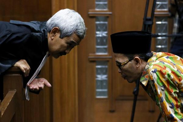 Terdakwa Kepala Kanwil Kemenag Jatim nonaktif Haris Hasanuddin (kanan) berbincang dengan kuasa hukumnya saat akan menjalani sidang tuntutan di Pengadilan Tipikor, Jakarta, Rabu (17/7/2019). - ANTARA FOTO/Rivan Awal Lingga