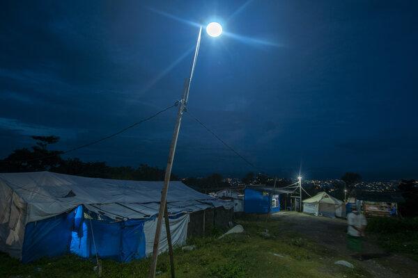 Warga beraktivitas di jalan yang diterangi dengan listrik tenaga surya di kompleks pengungsian Kelurahan Balaroa, Palu, Sulawesi Tengah, Sabtu (13/7/2019). Pemanfaatan tenaga surya untuk penerangan di kompleks pengungsian itu sangat membantu korban bencana dalam pemenuhan kebutuhan energi listrik yang sangat terbatas dan disubsidi oleh pemerintah setempat. - Antara/Basri Marzuki