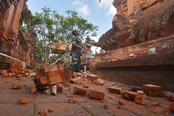 Prajurit TNI memantau kerusakan pada bagian candi yang runtuh akibat gempa di Pura Lokanatha, Denpasar, Bali, Selasa (16/7/2019). - ANTARA/Nyoman Budhiana