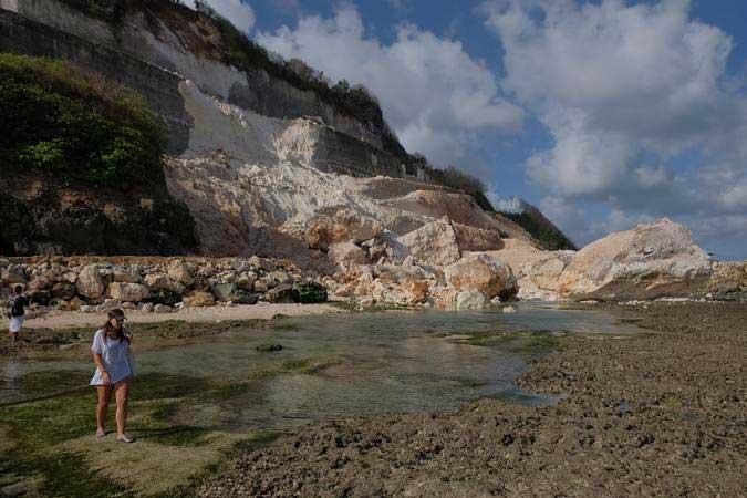 Wisatawan melintas di dekat reruntuhan tebing akibat gempa bumi di kawasan objek wisata Pantai Melasti, Badung, Bali, Selasa (16/7/2019). - ANTARA/Nyoman Hendra Wibowo