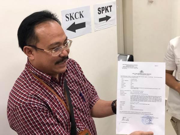 Hakim Sunarso memperlihatkan bukti pelaporan atas Desrizal, kuasa hukum Tomy Winata, yang menganiaya dirinya. - Bisnis/Sholahuddin Al Ayyubi