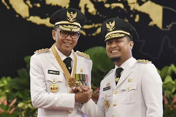 Gubernur Sulawesi Selatan Nurdin Abdullah (kiri) bersama Wakil Gubernur Sudirman Sulaiman melakukan salam komando usai pelantikan di Istana Negara, Jakarta, Rabu (5/9/2018). - ANTARA/Puspa Perwitasari