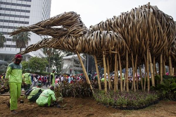 Petugas Suku Dinas Kehutanan Jakarta Pusat mengganti tanaman yang rusak di sekitar instalasi bambu Getah Getih, Jakarta, Minggu (23/6/2019). - ANTARA FOTO/Dhemas Reviyanto