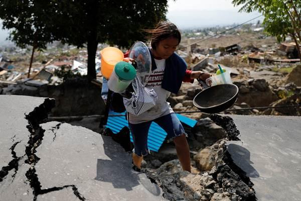 Ilustrasi - Seorang anak membawa barang yg masih bisa diselamatkan dari reruntuhan rumahnya pascagempa, di Balaroa, Palu, Sulawesi Tengah, Kamis (5/10/2018). - Reuters/Beawiharta