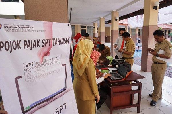 Pegawai Negeri Sipil (PNS) Pemerintah Kota Tangerang menyerahkan laporan SPT kepada petugas Pajak, Tangerang, Banten, Senin (27/3). - Antara/Fajrin Raharjo