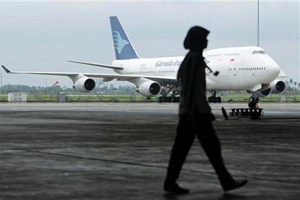 Seorang karyawan GMF AeroAsia melintas di dekat pesawat Boeing 747 Garuda Indonesia - Reuters/Beawiharta