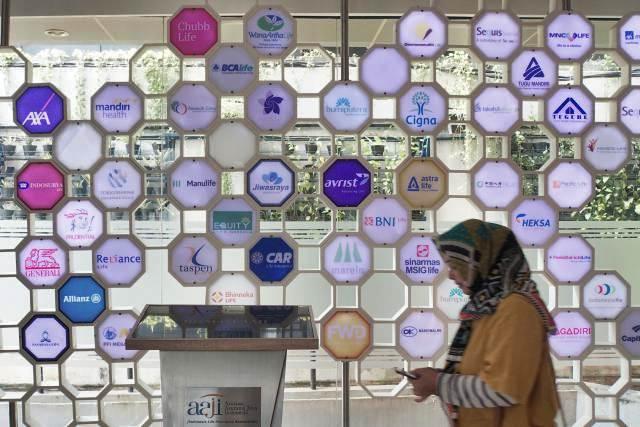 Pengunjung beraktivitas di dekat logo asuransi jiwa di gedung Asosiasi Asuransi Jiwa Indonesia (AAJI), Jakarta - Bisnis/Himawan L Nugraha