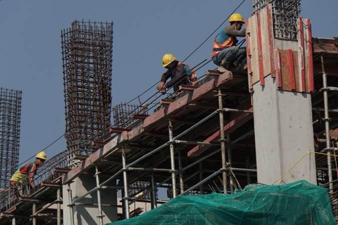 Pekerja menyelesaikan proyek pembangunan Transit Oriented Development (TOD) atau rumah susun terintegrasi dengan sarana transportasi yang berdekatan dengan stasiun kereta rel listrik (KRL) Commuterline Tanjung Barat  di Jakarta, Kamis (11/7/2019). - Bisnis/Himawan L Nugraha