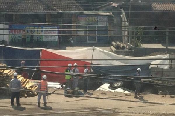 Roda belakang mobil yang terperosok di lubang galian proyek jalan lintas bawah Kentungan, masih coba dievakuasi petugas, Selasa (23/7/2019). - Harian Jogja/Yogi Anugrah