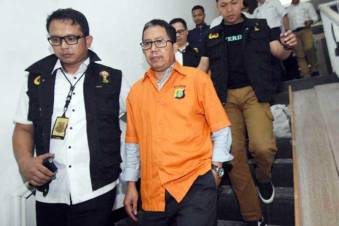 Mantan Plt.Ketua Umum PSSI Joko Driyono (tengah) mengenakan rompi tahanan, usai menjalani pemeriksaan di Ditreskrimum Polda Metro Jaya, Jakarta, Selasa (26/3/2019) dinihari. - ANTARA/Indrianto Eko Suwarso