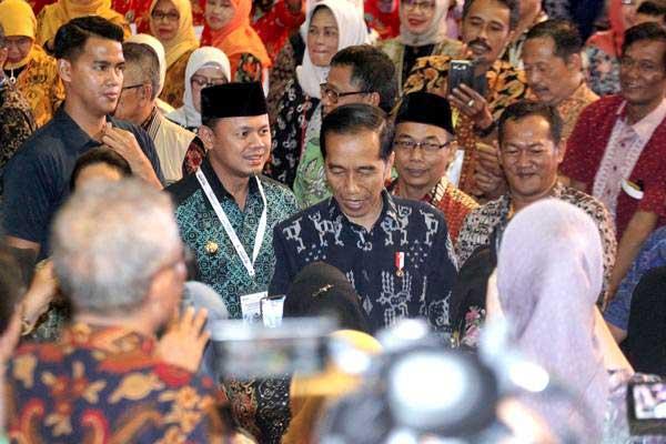Presiden Joko Widodo (tengah) didampingi Wali Kota Bogor Bima Arya (kedua kiri) menghadiri acara Program Wirausaha ASN dan Pensiunan di SICC, Sentul, Bogor, Jawa Barat, Rabu (16/1/2019). - ANTARA FOTO/Yulius Satria Wijaya