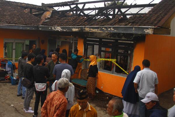 Warga melihat Tempat Kejadian Perkara (TKP) kebakaran di sebuah rumah di Junrejo, Batu, Jawa Timur, Rabu (24/7/2019). Kebakaran tersebut mengakibatkan empat orang anak tewas. - Antara/Ari Bowo Sucipto