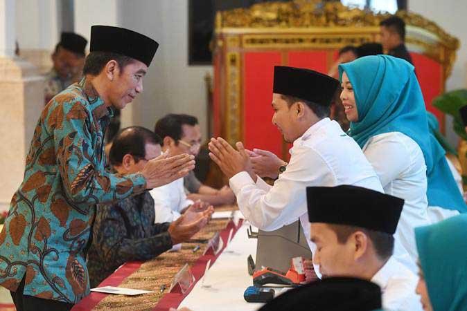 Presiden Joko Widodo (kiri) berjabat tangan dengan petugas usai melakukan pembayaran zakat mal di Istana Negara, Jakarta, Kamis (16/5/2019). Presiden membayar zakatnya sebesar Rp55 juta. - ANTARA/Akbar Nugroho Gumay