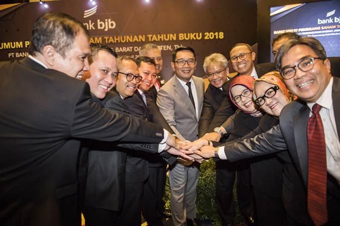 Gubernur Jawa Barat Ridwan Kamil (tengah) didampingi Direktur Utama Bank bjb terpilih Yuddy Renaldi (kelima kanan) bertumpu tangan bersama dengan jajaran Direksi Bank bjb seusai RUPST di Bandung, Selasa (30/4/2019). - ANTARA/M Agung Rajasa