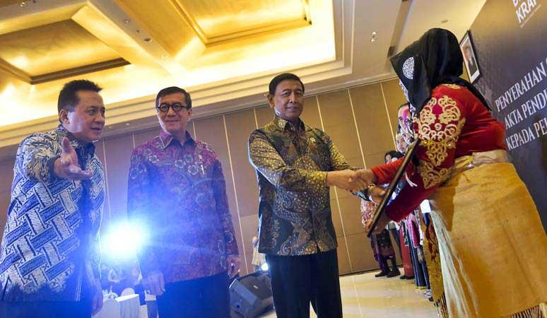 Menkopolhukam Wiranto (ketiga kiri) bersama Kepala Badan Ekonomi Kreatif (Bekraf) Triawan Munaf (kiri) dan Menkumham Yasonna Laoly (kedua kiri) menyerahkan sertifikat hak kekayaan intelektual kepada pelaku ekonomi kreatif di Jakarta, Senin (8/4/2019). - ANTARA/Galih Pradipta