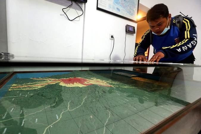 Petugas mengamati peta topografi daerah bahaya Gunung Tangkuban Parahu di Pos Pengamatan Gunung Api Tangkuban Parahu, Lembang, Kabupaten Bandung Barat, Jumat (26/7) malam. - Bisnis/Rachman