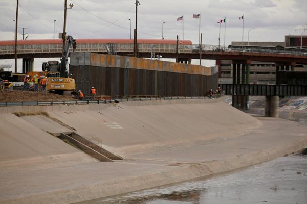 Polisi perbatasan Amerika Serikat dan pekerja proyek tembok perbatasan berdiri di dekat ekskavator proyek pembangunan tembok perbatasan antara El Paso dan Ciudad Juarez di wilayah Meksiko, Selasa (5/2/2019). - Reuers/Jose Luis Gonzalez