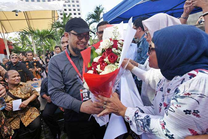 Penyidik KPK Novel Baswedan (tengah) menerima karangan bunga dari warga saat menghadiri peringatan dua tahun kasus kekerasan yang menimpanya di depan gedung KPK, Jakarta, Kamis (11/4/2019). - ANTARA/Indrianto Eko Suwarso