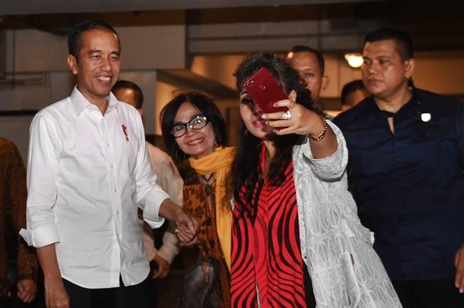 Presiden terpilih periode 2019-2024 Joko Widodo (kiri) menerima ajakan swafoto pendukungnya usai pertemuan dengan Tim Kampanye Nasional (TKN) di Jakarta, Jumat (26/7/2019). - ANTARA/Akbar Nugroho Gumay