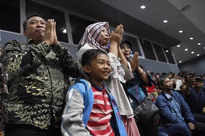 Ekspresi terpidana kasus pelanggaran Undang-Undang Transaksi dan Informasi Elektronik (UU ITE), Baiq Nuril Maknun (tengah) didampingi kerabat saat pengesahan amnesti untuk dirinya pada rapat paripurna DPR di Kompleks Parlemen Senayan, Jakarta, Kamis (25/7/2019). - ANTARA/Puspa Perwitasari