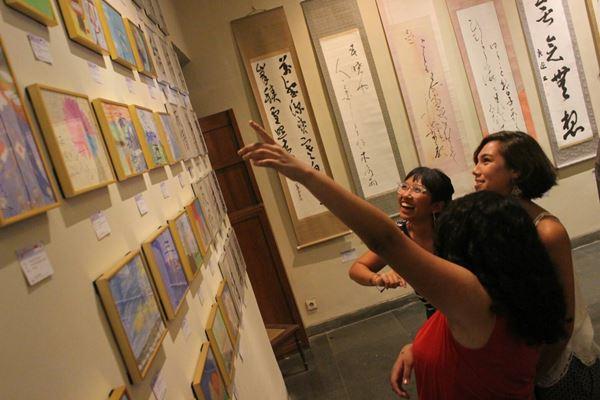 Pengunjung mengamati lukisan karya seniman Indonesia dan Jepang yang dipamerkan untuk memperingati 60 tahun hubungan diplomatik kedua negara di Danes Art Veranda, Jumat (24/8).  - Bisnis/Ni Putu Eka Wiratmini