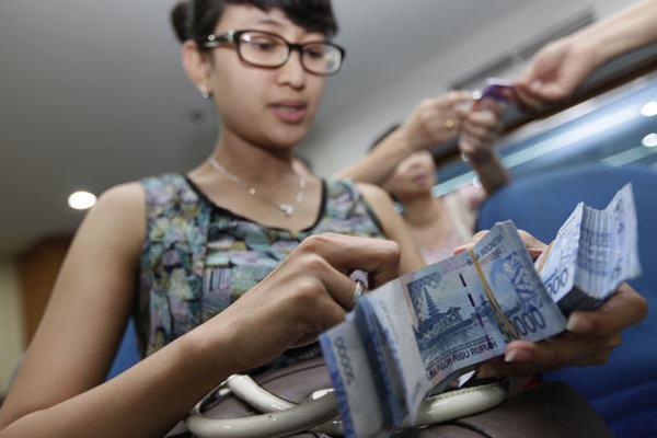 Seorang wanita tengah menghitung uang - Bloomberg