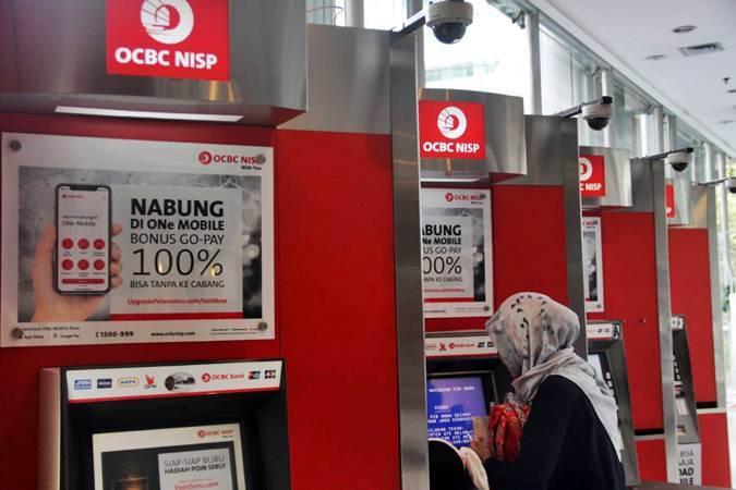 Nasabah melakukan transaksi di ATM Bank OCBC NISP, di Jakarta - Bisnis/Triawanda Tirta Aditya
