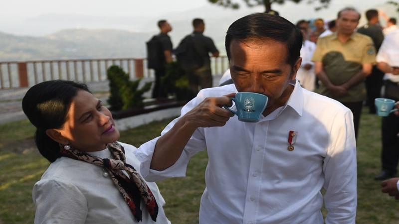 Presiden Joko Widodo (kanan) didampingi Ibu Negara Iriana Joko Widodo mencoba kopi lokal jenis Lintong Arabica saat mengunjungi kawasan Sipinsur Geosite di Kabupaten Humbang Hasundutan (Humbahas), Sumatera Utara, Senin (29/7/2019). - Antara