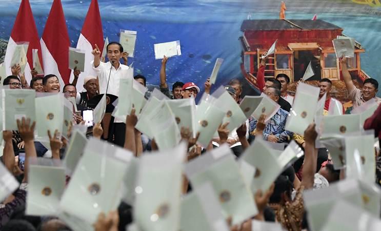 Presiden Joko Widodo (kiri) menyampaikan sambutan saat penyerahan sertifikat tanah. - ANTARA/Puspa Perwitasari