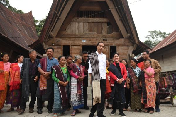 Presiden Joko Widodo (tengah) bersama Ibu Negara Iriana Joko Widodo (kelima kiri) mengunjungi kawasan kerajinan tenun ulos di Samosir, Sumut, Selasa (30/7/2019). - ANTARA FOTO/Nugroho Gumay