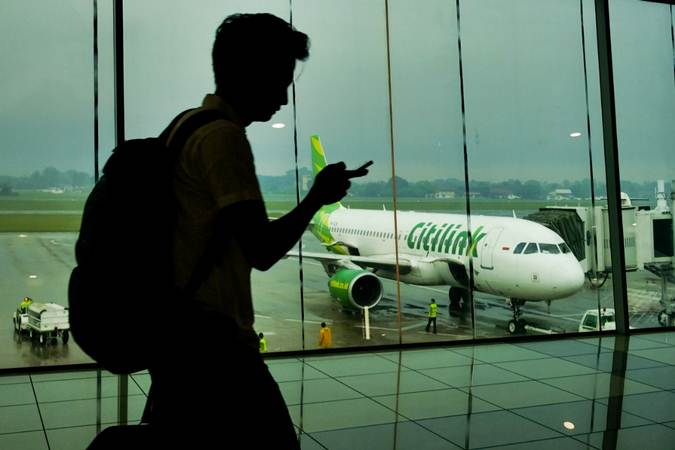 Penumpang berjalan di dekat pesawat Citilink Indonesia di Bandara Sultan Mahmud Badaruddin II, Palembang, Sumatra Selatan - Bisnis/Felix Jody Kinarwan