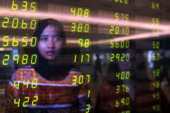 Ilustrasi. Karyawan berada di depan papan elektronik yang menampilkan harga saham di Jakarta, Senin (22/7/2019). - Bisnis/Abdullah Azzam