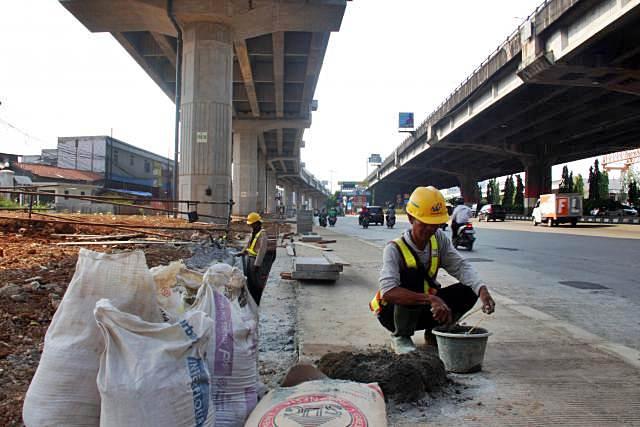 Pekerja menyelesaikan proyek pembangunan ruas jalan tol Becakayu di Jakarta, Selasa (16/7/2019). - Bisnis/Triawanda Tirta Aditya