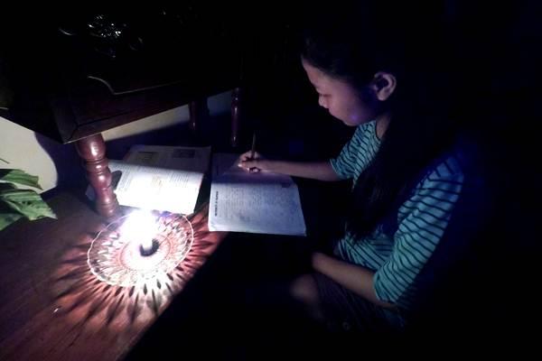 Seorang anak belajar dengan menyalakan lilin sebagai alat bantu penerangan saat listrik padam, di Kota Gorontalo, Gorontalo, Minggu (6/1/2019). - ANTARA/Adiwinata Solihin