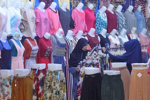 Calon pembeli memilih pakaian baru di pusat pejualan pakaian jadi di Desa Gampa, Kecamatan Johan Pahlawan, Aceh Barat, Aceh, Senin (19/6). - Antara/Syifa Yulinnas