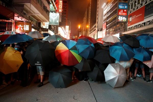 Para pengunjuk rasa yang menuntut dihapuskannya RUU Ekstradisi menggunakan payung ketika berhadapan dengan polisi anti huru hara di dekat Mongkok, Hong Kong, Minggu (7/7/2019). - Reuters/Thomas Peter