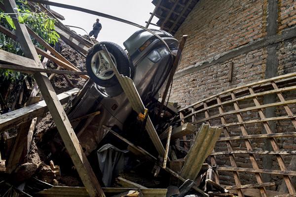 Warga mengamati rumah dan mobil yang rusak akibat longsor di Desa Banaran, Kecamatan Pulung, Ponorogo, Jawa Timur, Minggu (2/4). - Antara/Zabur Karuru