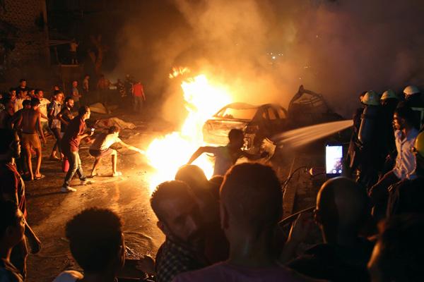 Warga bergotong royong memadam api akibat tabrakan mobil di dekat Institut Nasional Kanker Kairo, yang terjadi Minggu malam 4 Agustus 2019 atau Senin pagi 5 Agustus WIB. - Reuters/Shokry Hussien.