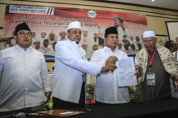 Ketua Gerakan Nasional Pengawal Fatwa Ulama (GNPF-U) Yusuf Muhammad Martak (tengah) bersama bakal calon presiden Prabowo Subianto (kanan) didampingi Wakil Ketua Umum Partai Gerindra Fadli Zon (kiri) menunjukkan naskah pakta intregitas yang telah ditandatangani dalam acara Ijtima Ulama II dan Tokoh Nasional di Jakarta, Minggu (16/9). Ijtima Ulama II yang digelar GNPF-U menyepakati dukungan kepada pasangan Prabowo Subianto-Sandiaga Uno pada Pilpres 2019. - Antara