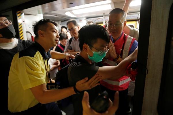 Petugas Mass Transit Railway (MTR) berupaya mencegah seorang pengunjuk rasa menghalangi pintu kereta, di tengah aksi unjuk rasa yang mencoba mengganggu layanan MTR di Stasiun Fortress Hill, Hong Kong, China, Senin (5/8/2019). - Reuters/Kim Kyung/Hoon