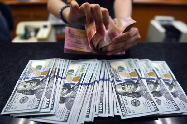 Petugas menghitung mata uang rupiah dan dolar AS di salah satu tempat penukaran uang di Jakarta, Selasa (9/10/2018). - ANTARA/Akbar Nugroho Gumay