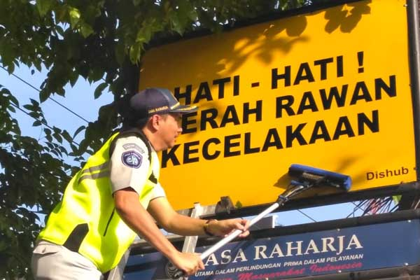 Kepala PT Jasa Raharja Kalsel M Zulham Pane saat membersihkan salah satu papan rambu lalu lintas - Arief Rahman