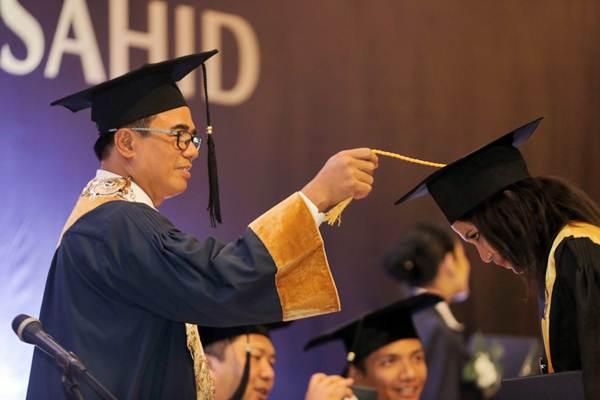 Ketua Sekolah Tinggi Pariwisata Sahid Jakarta Kusmayadi memindahkan tali toga wisudawan dalam acara Wisuda ke XXXIII Sekolah Tinggi Pariwisata Sahid Jakarta 2018, di Jakarta, Rabu (17/10/2018). - JIBI/Felix Jody Kinarwan