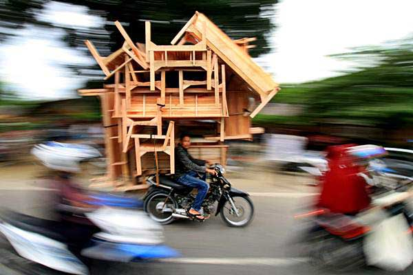 Pedagang membawa mebel kayu dengan becak motor hingga melebihi kapasitas, di Lhokseumawe, Aceh, Kamis (21/9). - ANTARA/Rahmad
