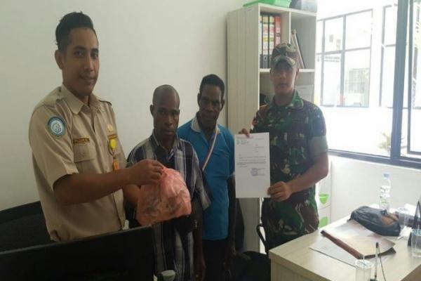 Anggota Satgas Pamtas Yonif 328/DGH saat menyerahkan barang bukti berupa dua kilogram gelembung ikan yang dibawa LS berkebangsaan PNG tanpa dilengkapi surat-surat kepada petugas karantina perikanan, di PLBN Skouw, Kamis (8/8/2019)./ANTARA-Dok.Yonif 328 - DGH)