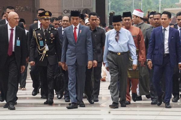 Presiden Republik Indonesia Joko Widodo (ketiga kiri) dan Perdana Menteri Malaysia Tun Dr Mahathir Mohamad (keempat kiri) berjalan bersama ke arah Masjid Putra Putrajaya, Malaysia, Jumat (9/8/2019) untuk melakukan salat Jumat bersama. Sebelumnya kedua pemimpin melakukan pertemuan bilateral terbatas di Kantor Perdana Menteri Putrajaya. - Antara/Agus Setiawan