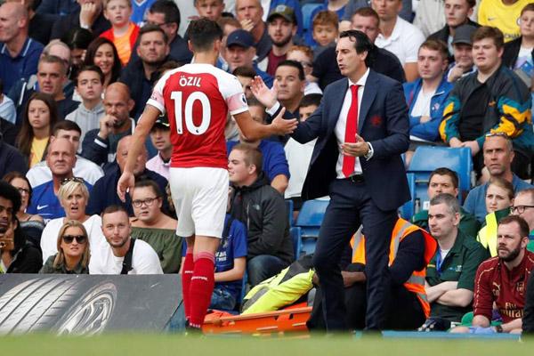 Pelatih Arsenal Unai Emery (kanan) dan Mesut Ozil. - Reuters