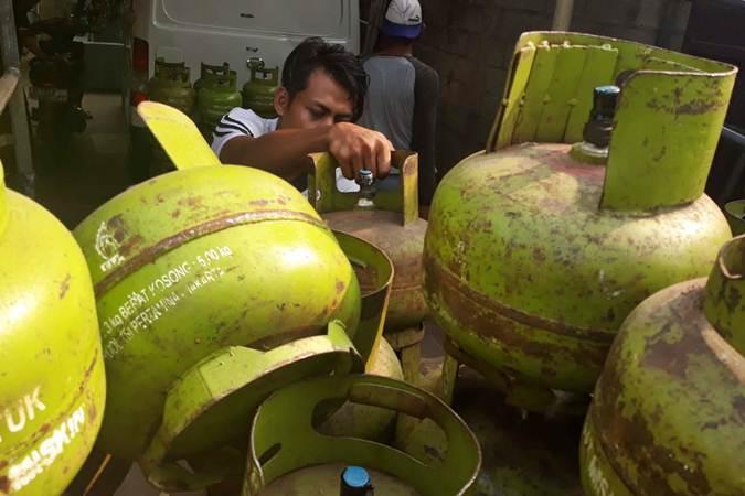 Pekerja membongkar tabung gas LPG 3kg di salah satu agen penjualan, di Jakarta - Bisnis/Endang Muchtar