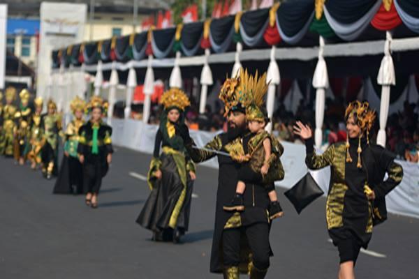"""Peserta mengikuti Artwear Carnival, salah satu karnaval pada ajang Jember Fashion Carnaval (JFC) di Jember, Jawa Timur, Jumat (11 - 8). Artwear Carnival adalah karnaval yang menampilkan pakaian dengan desain bertema kemenangan atau \""""victory,\"""" rangkaian dari JFC ke/16. ANTARA FOTO / Seno"""